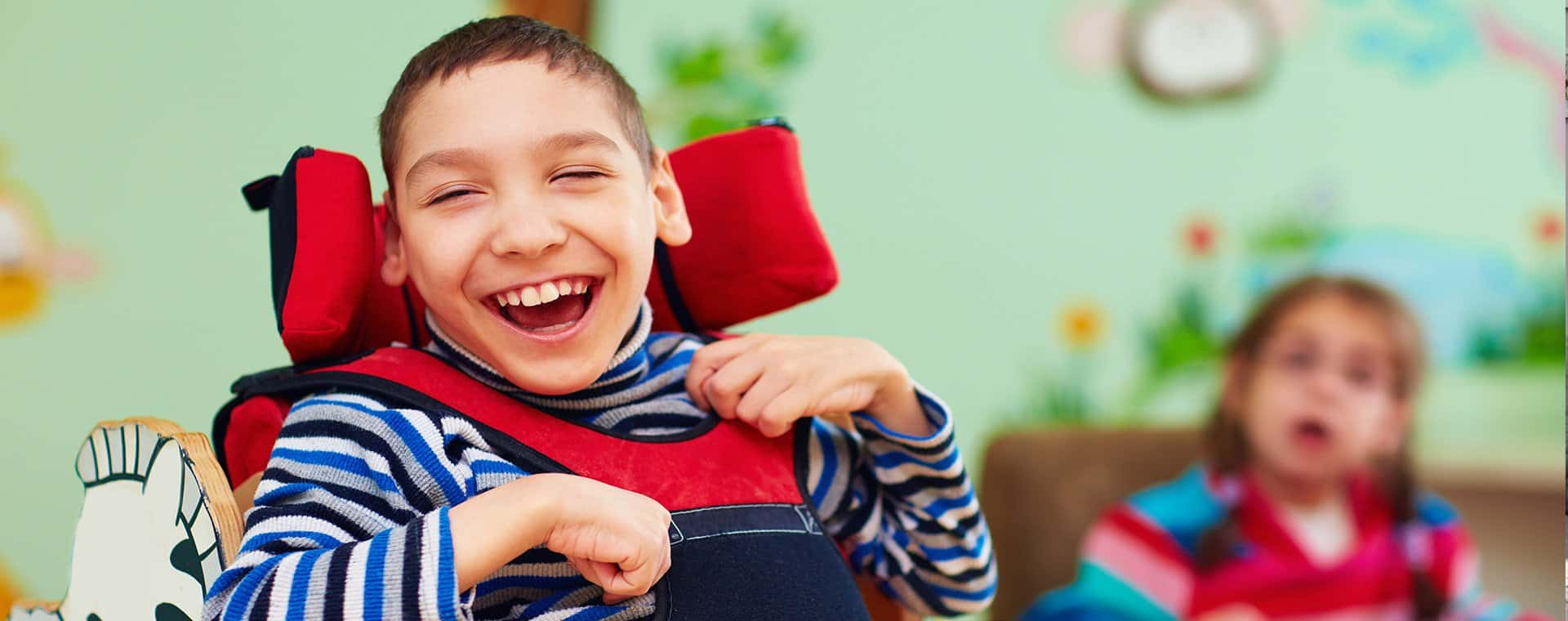 child in wheelchair laughing