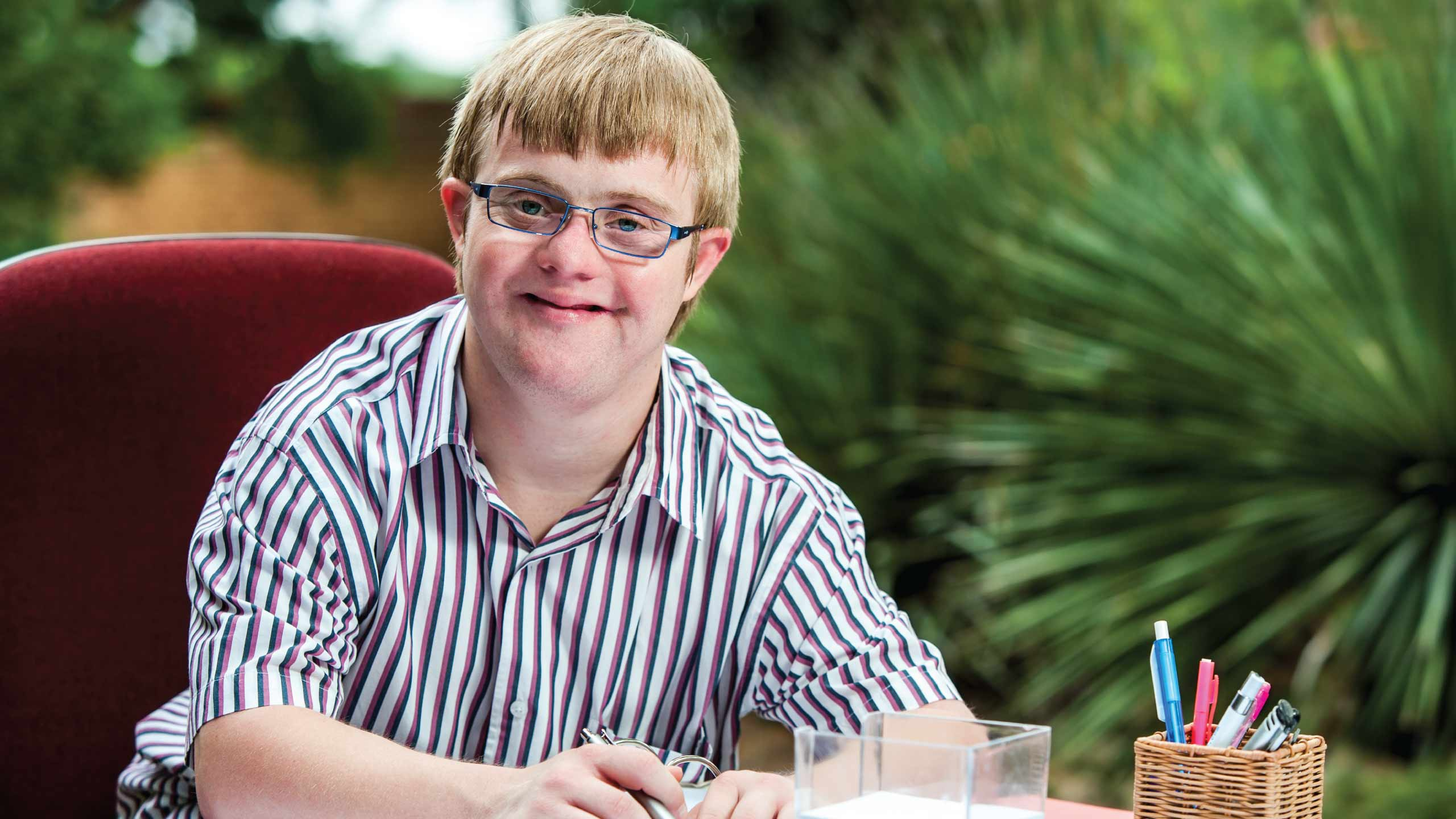 Young man with disability doing school work