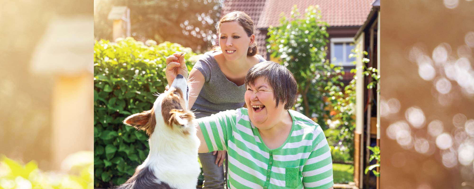 Person with disability and carer patting dog outdoors
